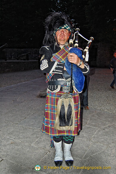 A lone piper plays as guests arrive